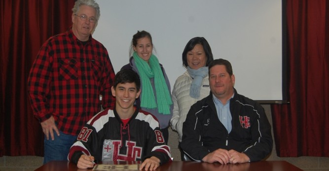 Mike Pilcher poses for a photo with his family and coach Schmatz